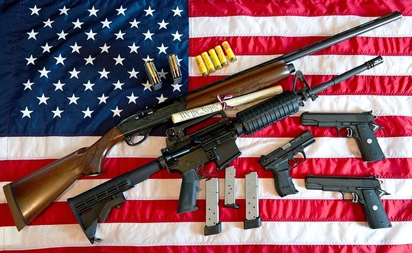 """This February 4, 2013 photo illustration in Manassas, Virginia, shows a Remington 20-gauge semi-automatic shotgun, a Colt AR-15 semi-automatic rifle, a Colt .45 semi-auto handgun, a Walther PK380 semi-auto handgun and various ammunition clips with a copy of the US Constitution on top of the American flag. US President Barack Obama Monday heaped pressure on Congress for action """"soon"""" on curbing gun violence. Obama made a pragmatic case for legislation on the contentious issue, arguing that just because political leaders could not save every life, they should at least try to save some victims of rampant gun crime. AFP PHOTO/Karen BLEIER (Photo credit should read KAREN BLEIER/AFP/Getty Images)"""